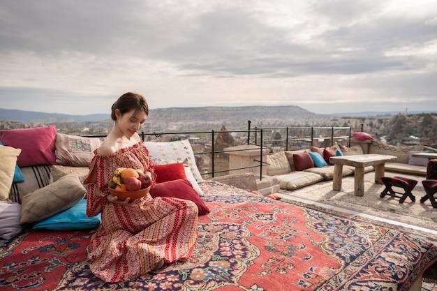 As mulheres felizes no telhado da caverna abrigam a apreciação do panorama da cidade de goreme, cappadocia turquia.