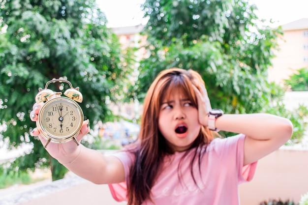 As mulheres ficam irritadas com o som do relógio, cobrindo os ouvidos e usando a outra mão para segurar o despertador dourado.