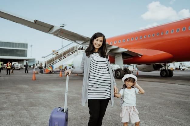 As mulheres grávidas e sua filha gostam de ficar ao lado do avião