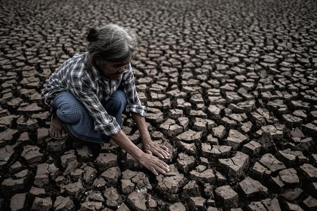 As mulheres idosas estão sentadas, olhando para as mãos, tocando o chão em clima seco, aquecimento global