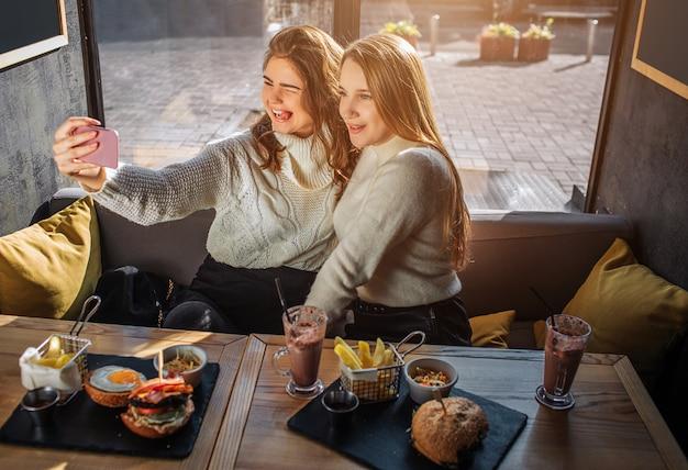 As mulheres jovens alegres sentam-se à mesa dentro no café e tomam selfie. eles se sentam juntos e posam. modelos sorriem. eles têm comida e bebida na mesa.