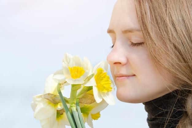 As mulheres jovens apreciam o buquê de narcisos, close-up