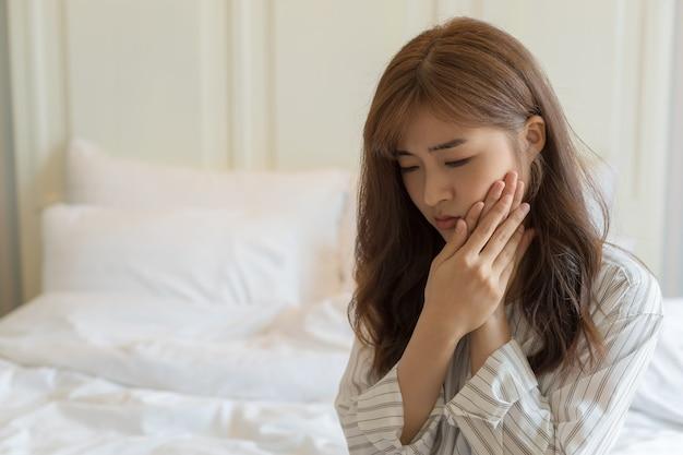 As mulheres jovens asiáticas têm dentes sensíveis, dores de dente, cáries ou gengivas inflamadas. saúde e conceito de pessoas doentes.