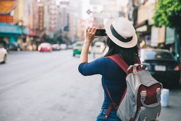 As mulheres jovens asiáticas tiram foto com mochileiro telefonando móvel na yaowarat road.