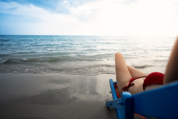 As mulheres jovens de biquíni relaxam na praia