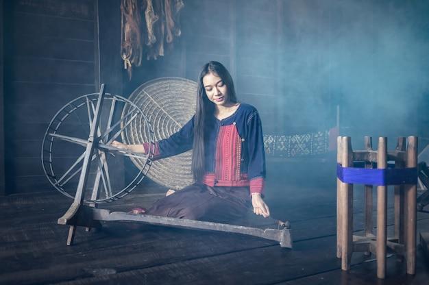 As mulheres jovens demonstram ao procedimento de fazer tecelagem de seda tailandesa na tailândia