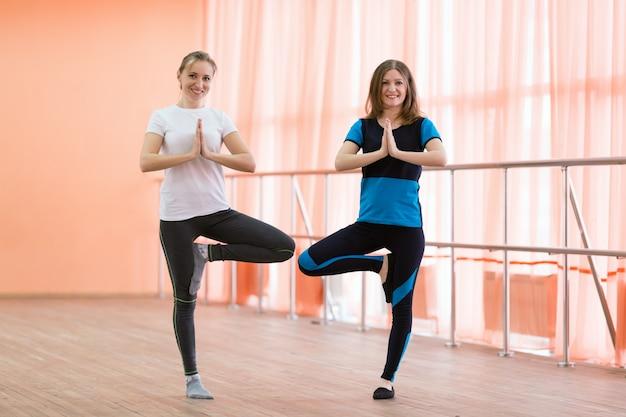 As mulheres jovens estão envolvidas em yoga.
