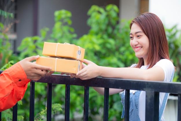 As mulheres jovens estão recebendo produtos on-line com alegria