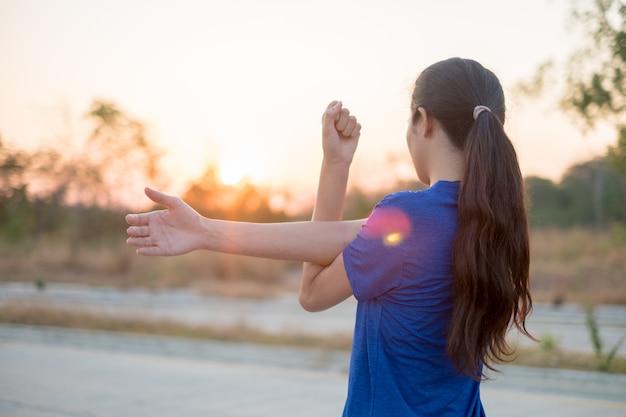 As mulheres jovens exercem antes de se exercitar no parque