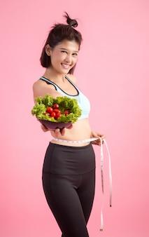 As mulheres jovens gostam de comer legumes em um rosa.