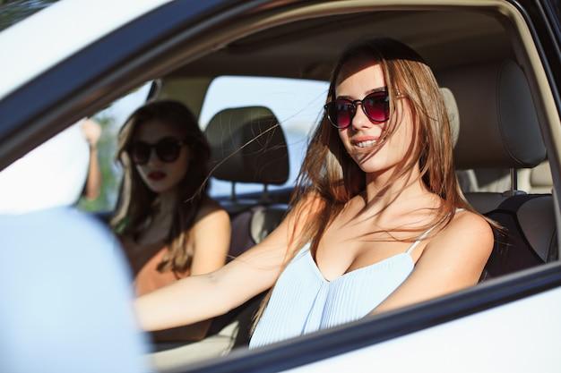 As mulheres jovens no carro sorrindo