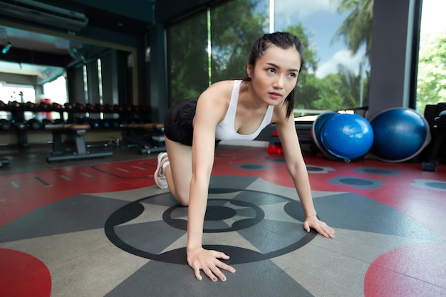 As mulheres jovens se aquecem antes de se exercitarem empurrando o chão e dobrando os joelhos no ginásio.