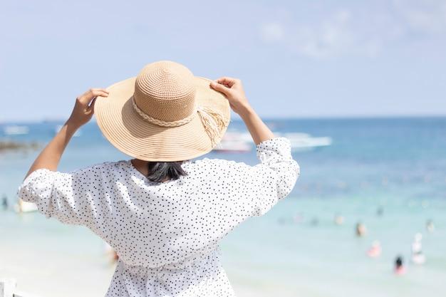 As mulheres jovens viajando relaxar na praia no verão