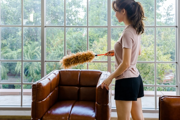 As mulheres limpam a casa com roupas e líquidos.