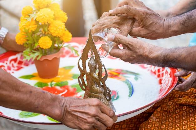 As mulheres mais velhas de mãos que derramam a água na estátua de buddha estão no dia de songkran