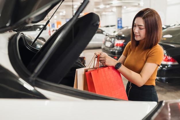 As mulheres mantêm sacolas de compras no carro