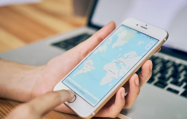 As mulheres mantêm um telefone com tela de exibição google maps