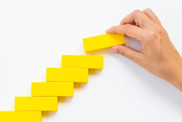 As mulheres mão colocar blocos de madeira amarelos em forma de uma escada