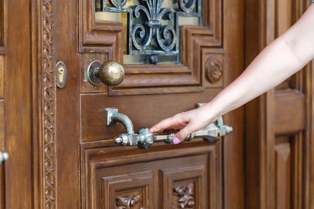 As mulheres mão maçaneta da porta aberta ou abrir a porta.