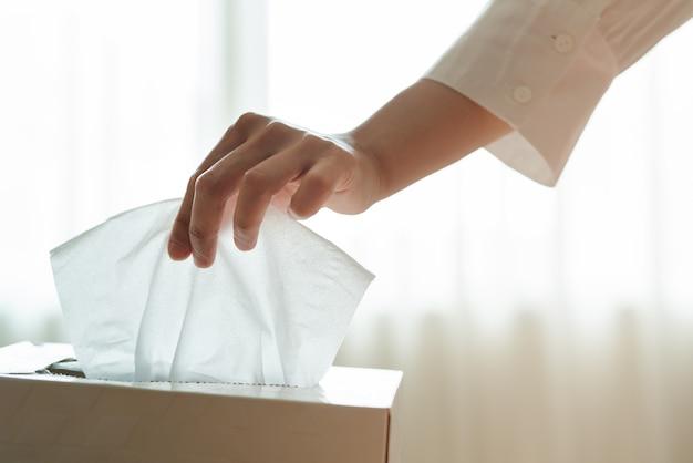 As mulheres mão pegando guardanapo / papel de seda da caixa de tecido