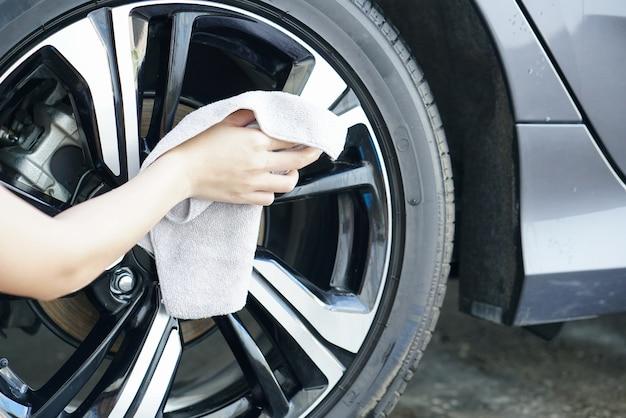 As mulheres mão seca limpando a superfície do carro com pano de microfibra após a lavagem.