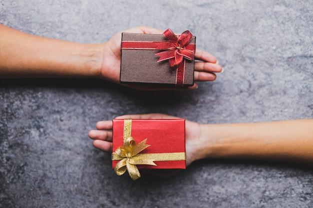 As mulheres mão segurando a caixa de presente marrom e uma caixa de presente vermelha dada a outra em uma mesa de pedra cinza
