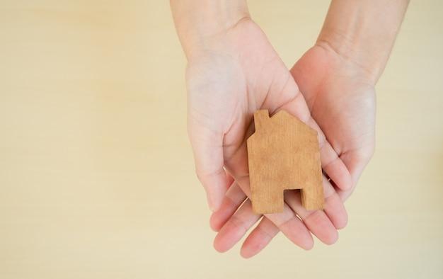 As mulheres mão segurando a decoração da casa de madeira, promovendo o trabalho em casa e o distanciamento social para reduzir a propagação da infecção por coronavírus. covid-19, distanciamento social e conceito de trabalhar em casa.