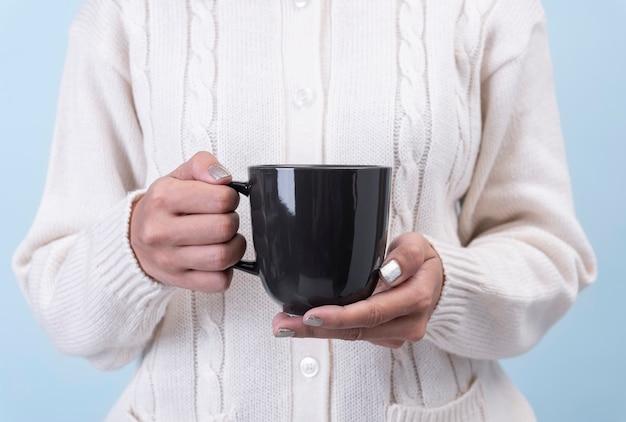 As mulheres mão segurando a xícara de café em cerâmica preta. maquete para mensagem de texto de publicidade criativa ou conteúdo promocional.