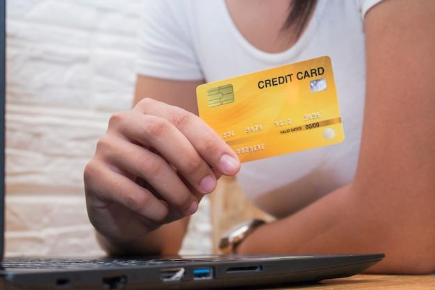 As mulheres mão segurando o cartão de crédito no café