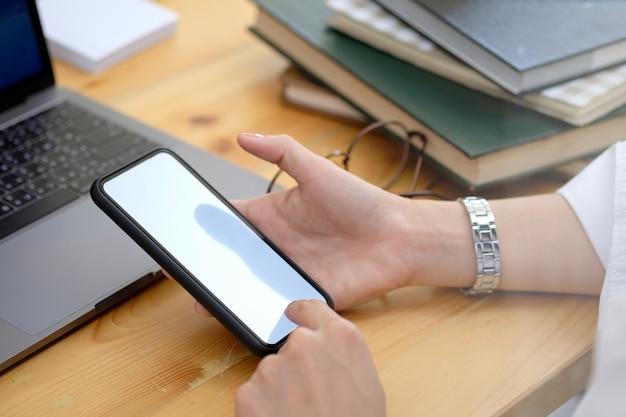 As mulheres mão segurando o smartphone com tela isolada acima da mesa no escritório