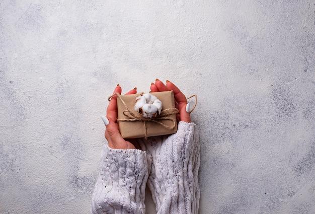 As mulheres mão segure caixas de presentes em papel ofício.