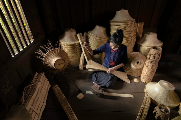 As mulheres novas estão tecendo na cesta handmade do campo de tailândia.