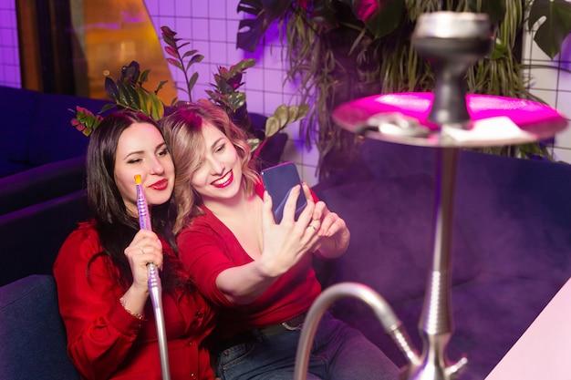 As mulheres novas na roupa vermelha fumam o cachimbo de água e tomam um selfie