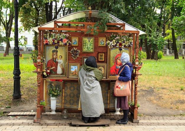 As mulheres ortodoxas rezam antes dos ícones no parque.