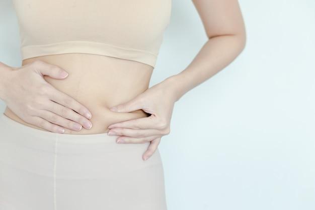 As mulheres pegam gordura no estômago para ver como ela reduziu a barriga. garota testando camada de gordura na cintura