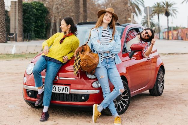 As mulheres perto do homem inclinando-se para fora do carro e mostrando o polegar para cima