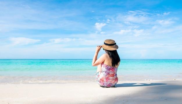 As mulheres que sentam-se para trás na praia e no mar têm um verão do feriado que relaxa