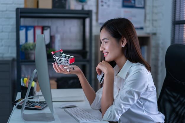 As mulheres que trabalham compram on-line com cartão de crédito, ela estava carregando um carrinho de compras