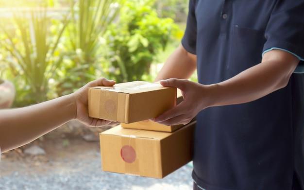 As mulheres receberão pacotes do pessoal de entrega profissional em segundo plano, desfocado