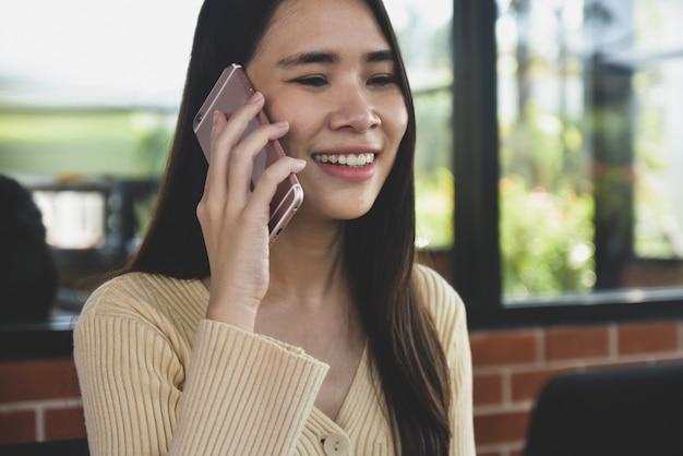 As mulheres são chamadas de celular, a garota está usando o telefone móvel esperto, as pessoas usam a comunicação por telefone