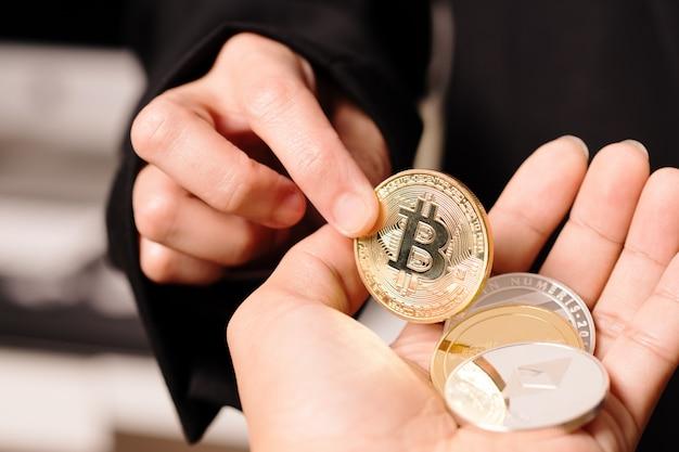 As mulheres seguram a moeda da criptomoeda na mão.