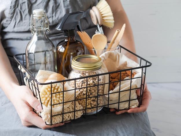 As mulheres seguram uma cesta de metal preto com conjunto de cozinha ecológica. alimentos, pincéis, utensílios de madeira, bolsas, garrafa e jarra.