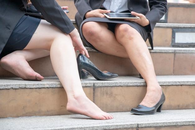 As mulheres sofrem de mordida de sapato ou pitada de sapato. ela tirou os sapatos.