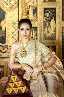 As mulheres tailandesas bonitas estão vestindo trajes nacionais tailandeses tradicionais.