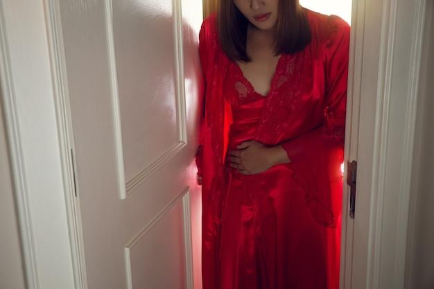 As mulheres têm dor de estômago por causa da diarreia no meio da noite. a mulher de camisola vermelha com robe de seda acorda para ir ao banheiro. o conceito com sintomas de problemas intestinais
