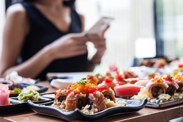 As mulheres tiram foto pelo celular sushi conjunto de comida japonesa no resturant