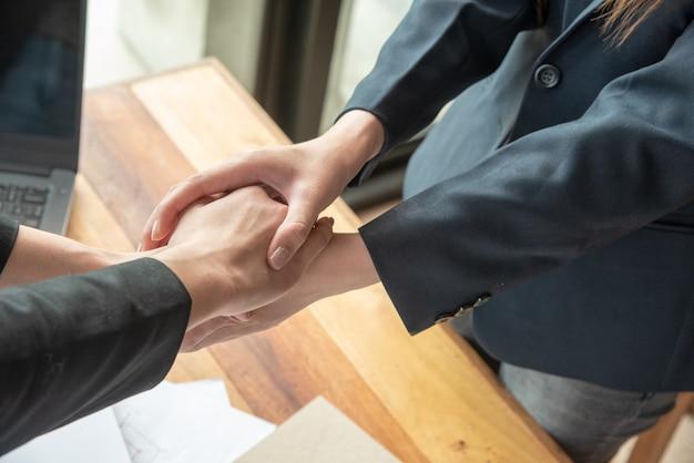 As mulheres tocam as mãos com sucesso de acordo