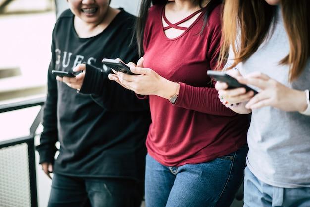 As mulheres tocam e conversando com telefone inteligente