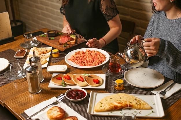 As mulheres tomam café da manhã com panquecas, crepes, omelete, geléia e chá