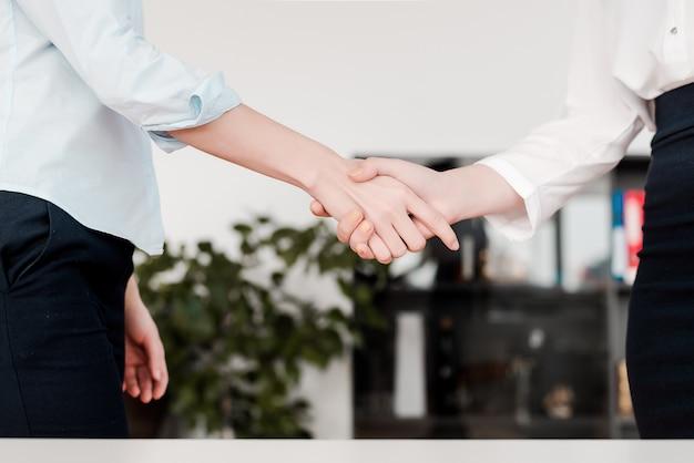 As mulheres trabalham no escritório juntos apertando as mãos